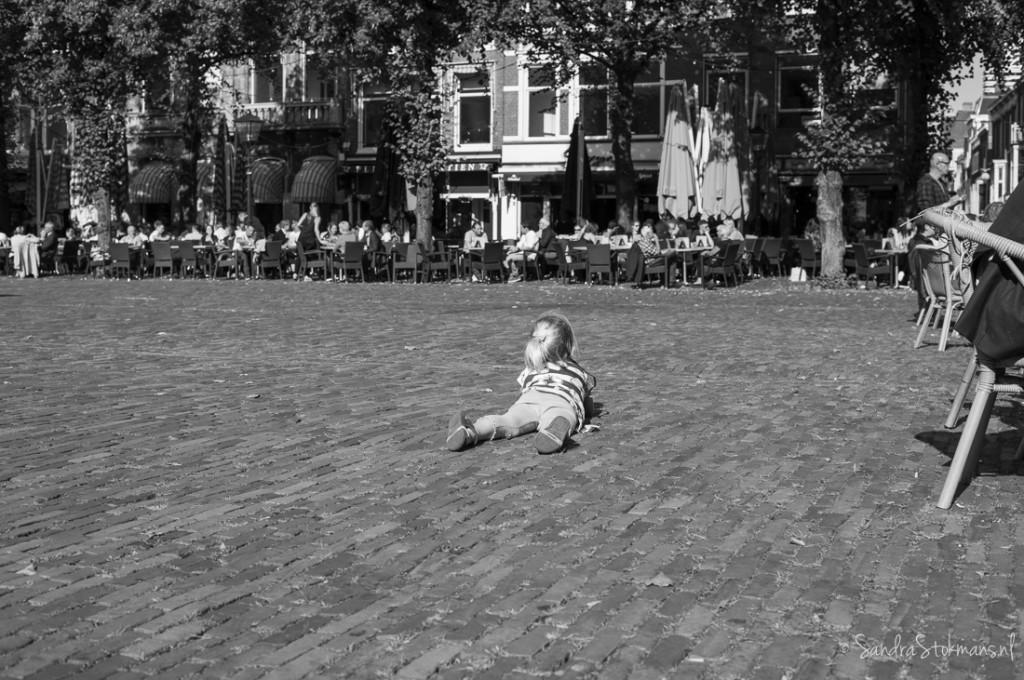 Meisje rust uit op Plein Den Haag na afloop initiatief van Liesje Doet voor de vluchtelingenproblematiek, straatfotografie Sandra Stokmans