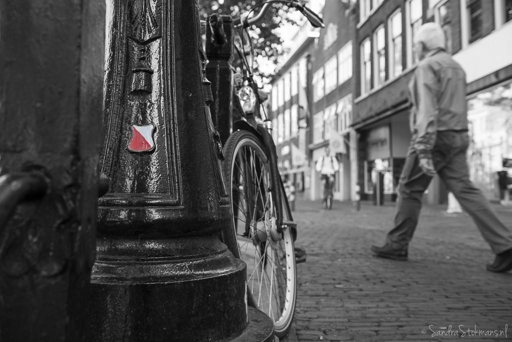 Vanuit laagstandpunt Oudegracht paaltje met Utrechts stadssymbool en fiets gefotografeerd in Utrecht, FotoJam 2015, by Sandra Stokmans