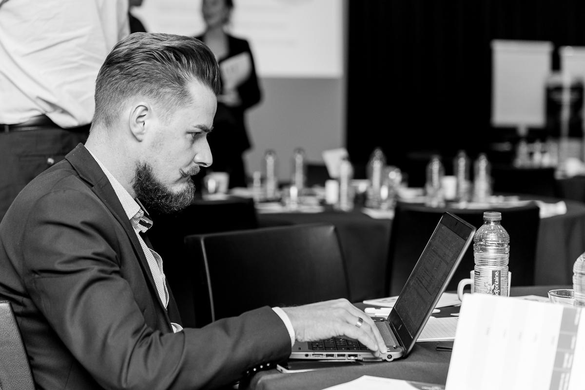 Een werkende zakenman met laptop tijdens het maken van een evenement reportage. Evenement fotografie, zakelijke fotografie, bedrijfsfotografie, image by Sandra Stokmans Fotografie