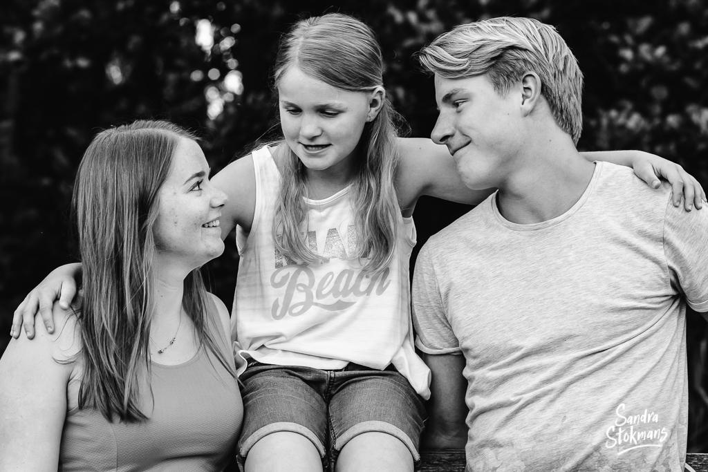 Familie foto van twee zussen en een broer zittend op een hek voor vaderdag, foto door Sandra Stokmans