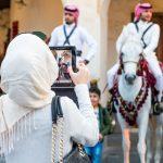 Vrouw maakt foto van kinderen en Qatari paarden met beetje versleten Ipad, reisfotografie Sandra Stokmans Fotografie