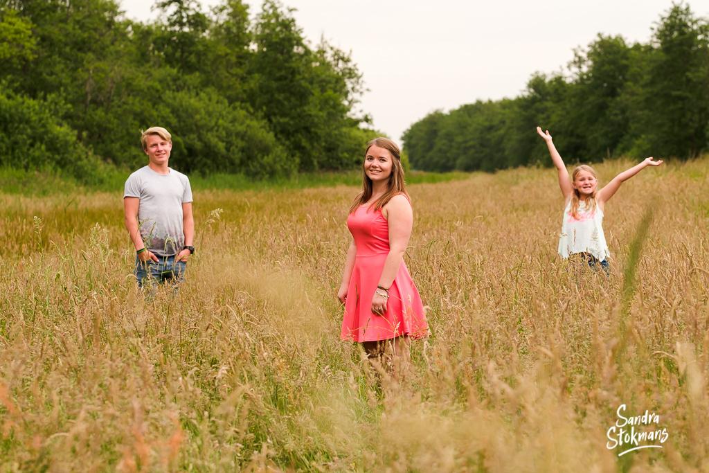 Familie shoot voor een vaderdag cadeau, foto van zussen en broer in een open veld, familie fotografie, foto door Sandra Stokmans Fotografie