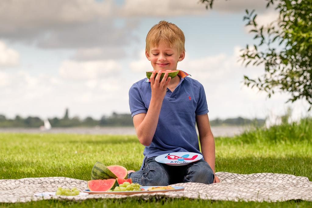 Jongetje wat op picknickkleed zit met bordje van KijkMijne op schoot. Eet een watermeloen. Foto voor de website door Sandra Stokmans Fotografie.