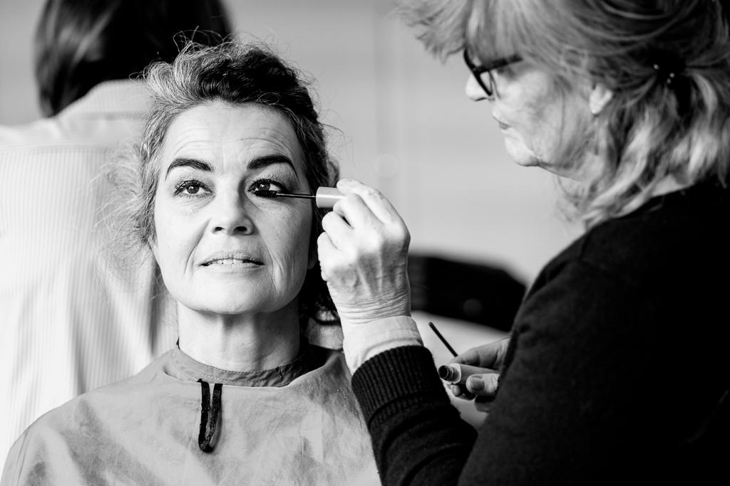Reportage fotografie door Sandra Stokmans Fotografie, tijdens een dag van het Vijftig Tinten Grijs project. Een van de dames wordt opgemaakt.