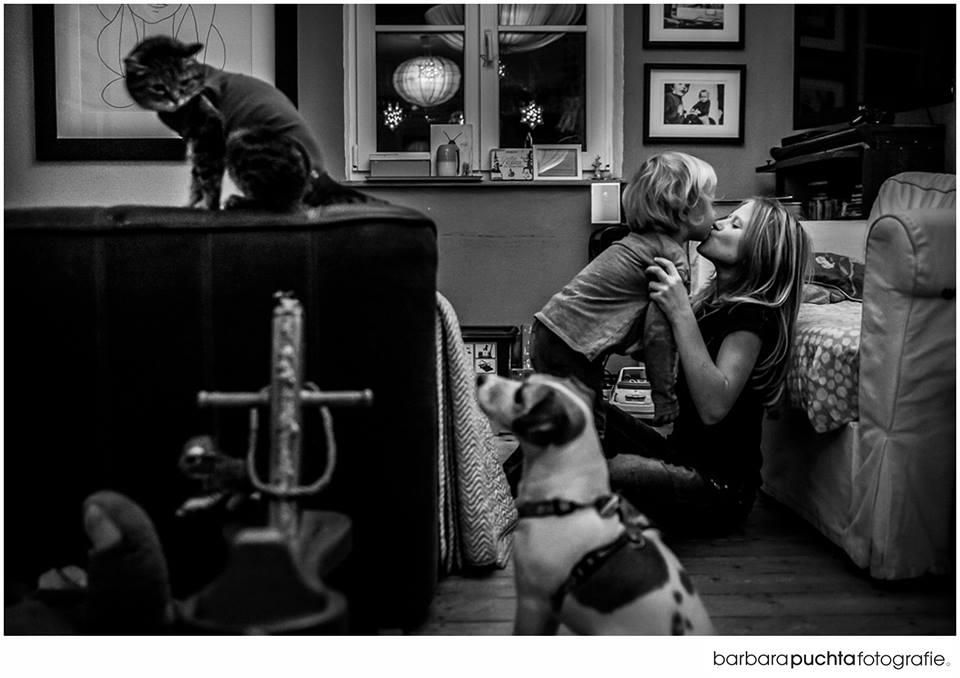 Moeder kust kind en op achtergrond zitten hond en kat naar elkaar te kijken