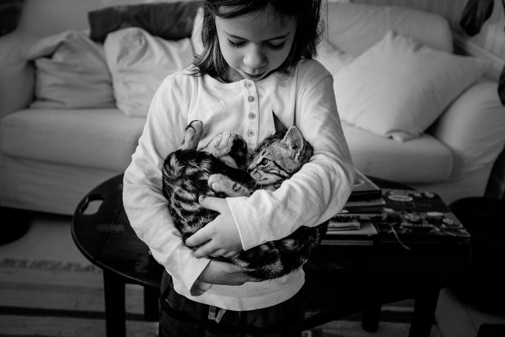 Meisje houdt poes in haar armen alsof het haar kindje is, foto door Caroline Holt, Girl holds kat as if it were her baby