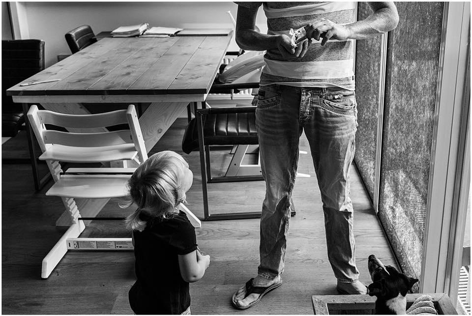 Vader is wat lekkers aan het pakken en kind en hond kijken toe, foto van Christie Agema Fotografie