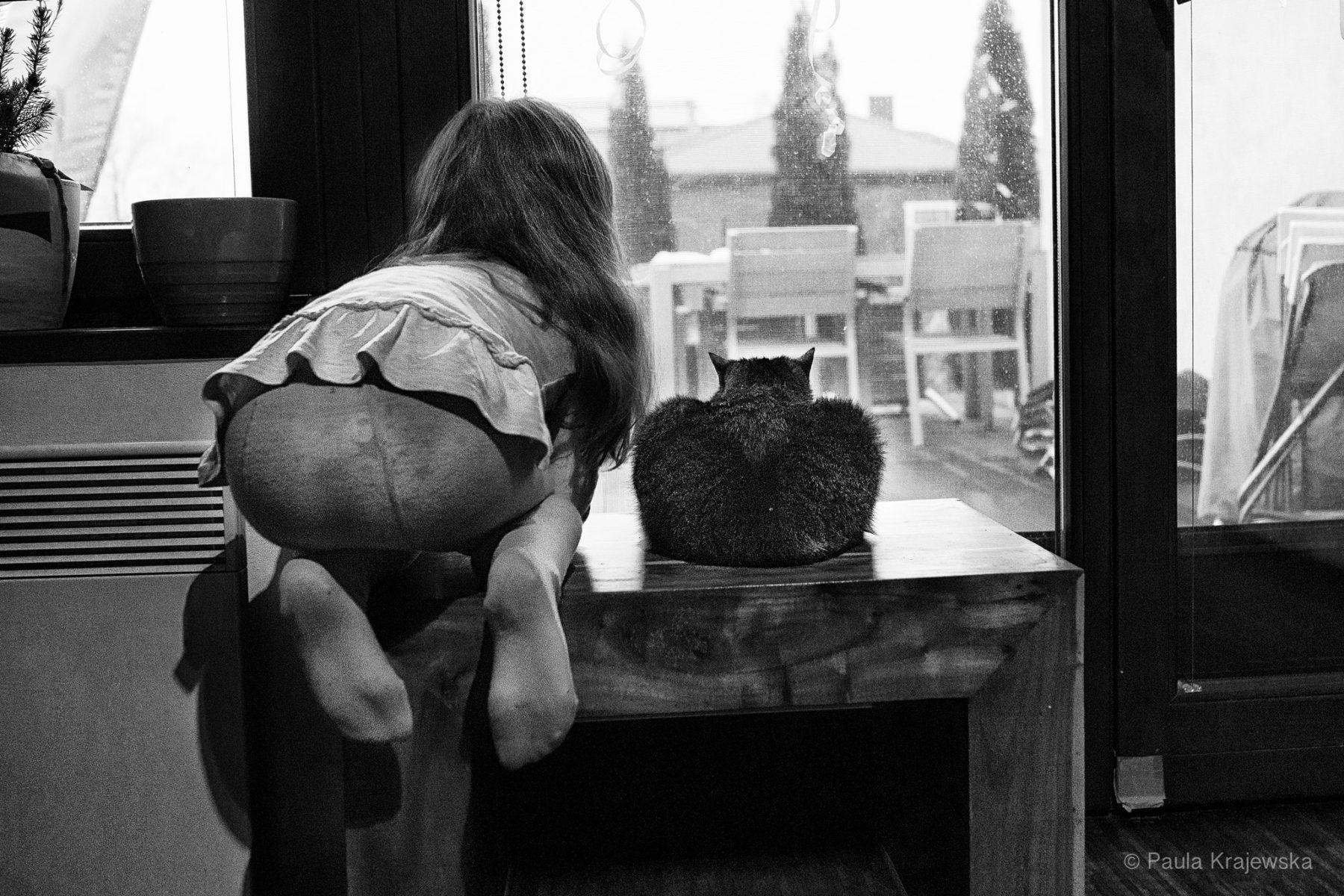 Meisje en kat op tafel kijkend naar het slecht weer buiten, foto door Paula Krajewska