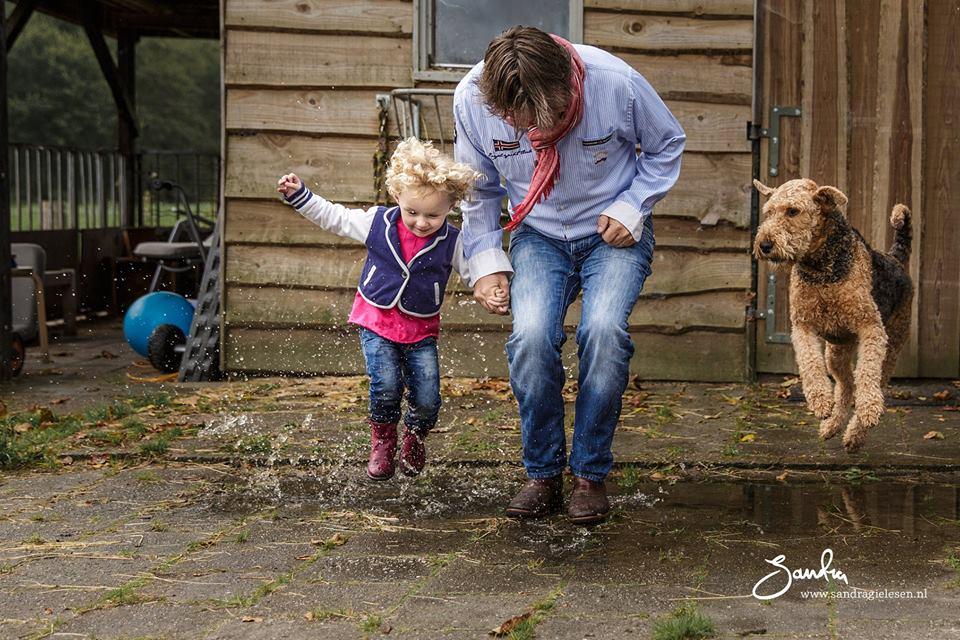 Moeder, kind en hond springen in een plas, foto door Sandra Gielesen-Roeling